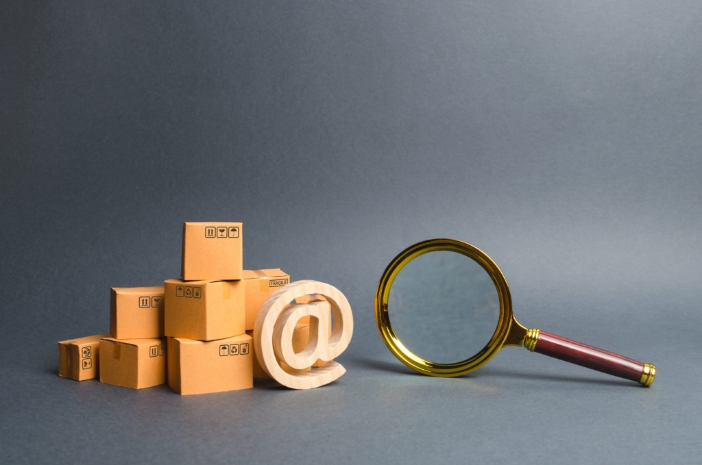 Pile of boxes with email symbol AT and a magnifying glass. Concept search for goods and services. Search for customers for sale, sales and retail. Tracking parcels via the Internet. Quality control