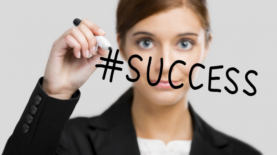Businesswoman drawing the hastgag #success on a glass board